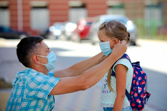 The father puts a surgical  masks on his daughter is face.