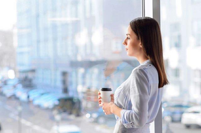 Pleasant sad woman standing near window